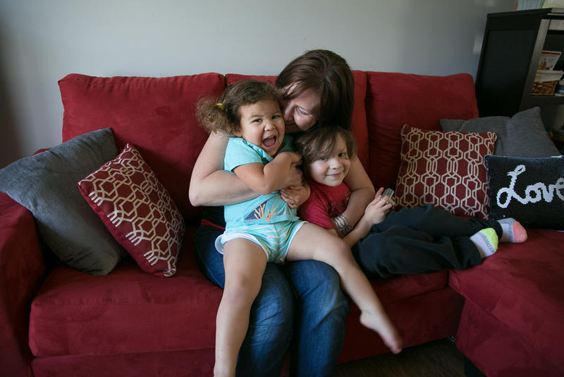 Jennifer Petrosky snuggles with her two children at her home in Dunbar