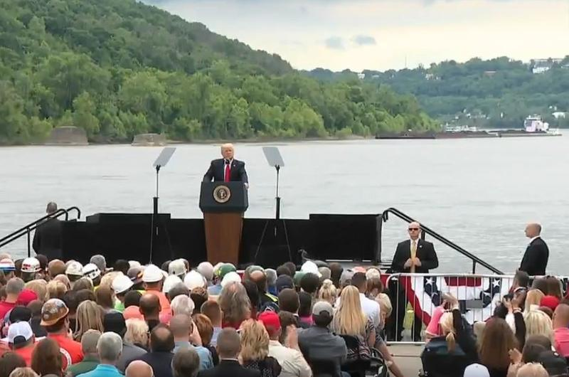 A coal barge passes as President Donald Trump speaks on the banks of the Ohio River.