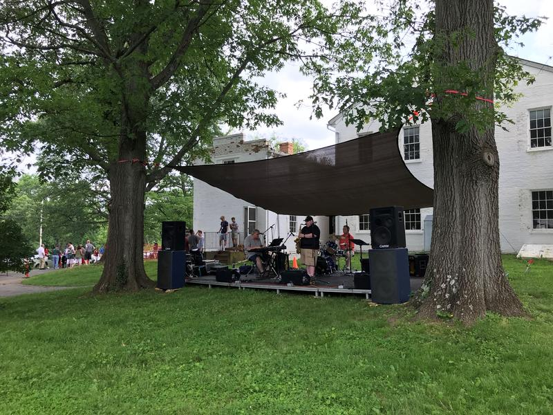 A group of musicians play jazz on the back lawn of the Happy Retreat mansion.