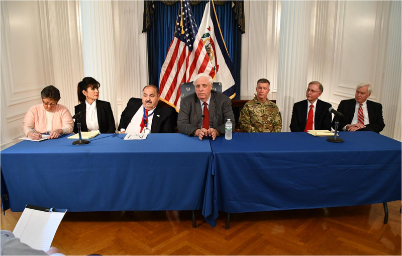 "Gov. Jim Justice (center) and other officials discuss a ""realignment"" in management of a slow-moving flood recovery program known as RISE West Virginia."