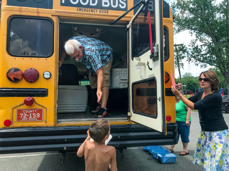 Kids grab lunch from the Food Bus during its daily stop at the Lewis County Park in Weston.