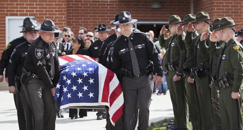 Members of the honor guard carry the body of the late Mingo County Sheriff Eugene Crum on Sunday, April 7, 2013, at the Mingo Central High School in Matewan, W.Va. following a memorial for the sheriff who was gunned down after just three months in office.