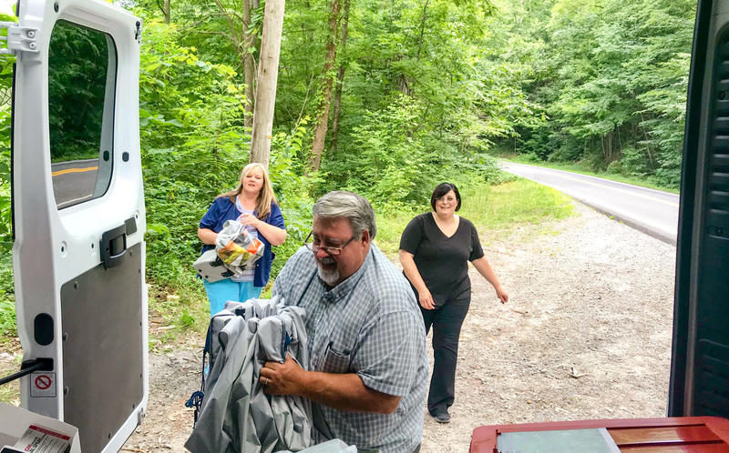 Crystal Simpson, Fred Cox and Gena Carter load up the Wyoming County mobile harm reduction unit van after providing services in Allen Junction, Wyoming County.