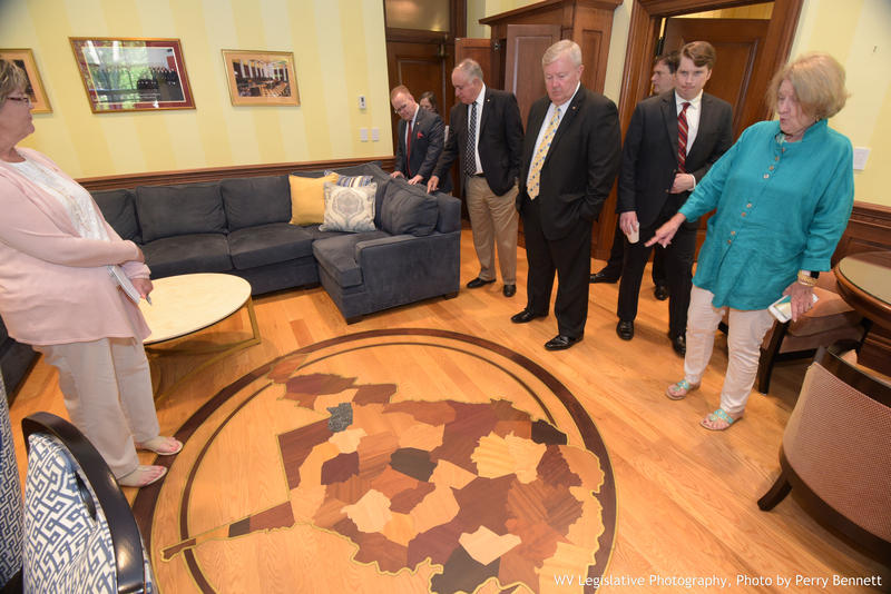 Members of the House Judiciary Committee look at a floor inlay in the office of suspended Justice Allen Loughry.
