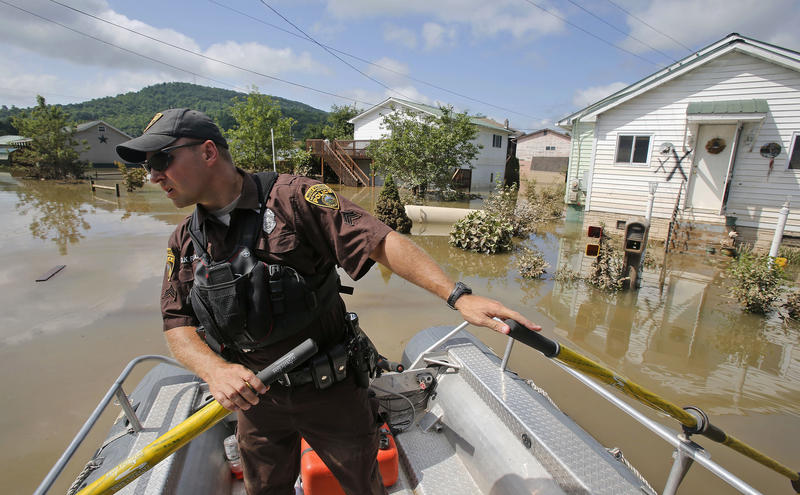 In this Saturday, June 25, 2016 file photo, Lt. Dennis Feazell, of the West Virginia Department of Natural Resources, watches for debris as he and a co-worker search flooded homes in Rainelle, W.Va.