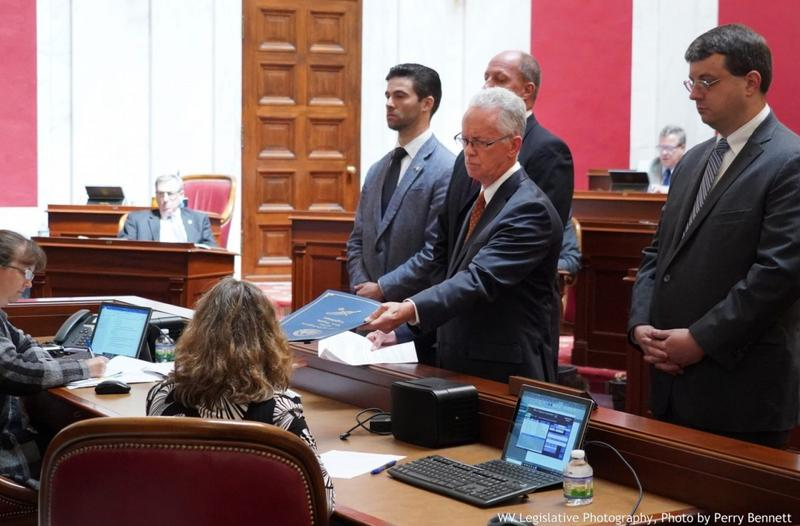 West Virginia House Judiciary Chairman Del. John Shott hands over the articles of impeachment to the Senate last month.