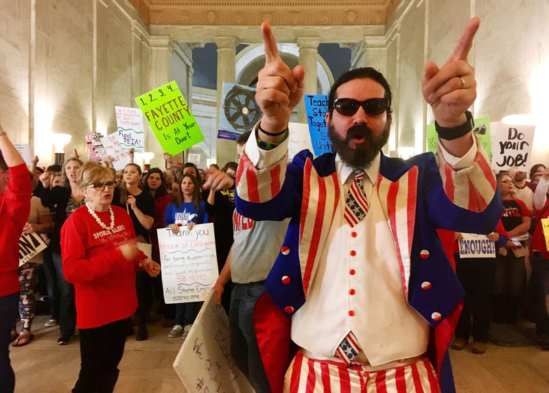 In this March 1, 2018 file photo, Parry Casto, a fifth grade teacher at the Explorer Academy in Huntington, W.Va., dressed in an Uncle Sam costume leads hundreds of teachers in chants outside the state Senate chambers at the Capitol in Charleston.