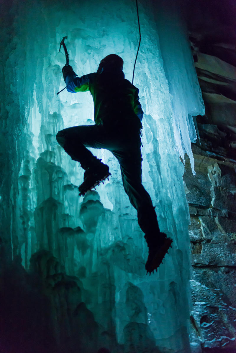 An ice climber scales a formation at night.