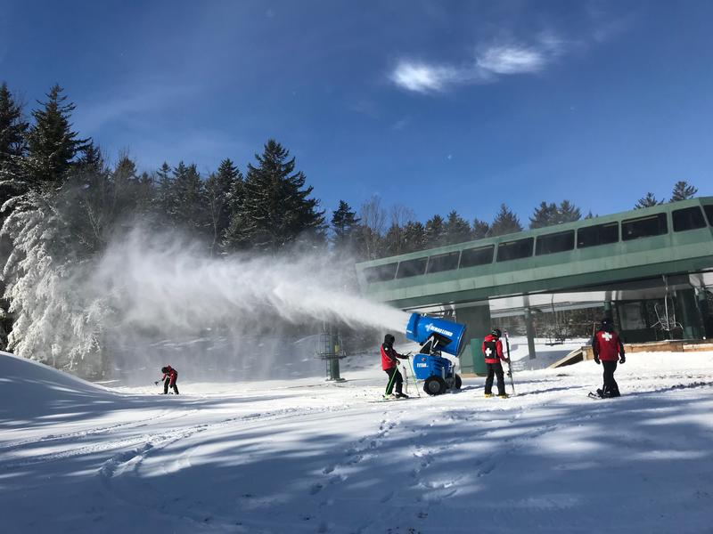 Skiers zoom past a snowmaking machine at Snowshoe Mountain Resort.