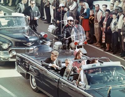 President and Mrs. John F. Kennedy smile at the crowds lining their motorcade route in Dallas, Texas, on November 22, 1963. Minutes later the President was assassinated as his car passed through Dealey Plaza.