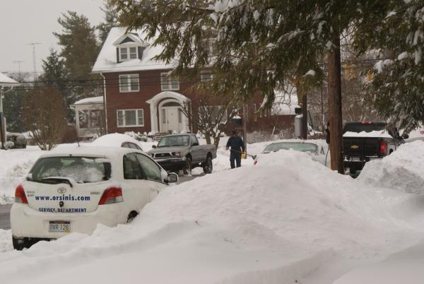 A Martinsburg resident clears the snow so he can get his vehicle out.