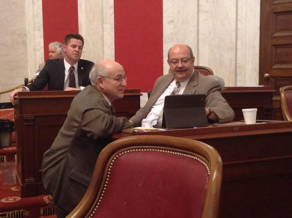Senate Finance Chair Roman Prezioso discusses legislation with Senator Doug Facemire on the state Senate floor.