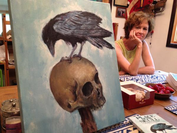 Painter Cecy Rose looks onto her painting that serves as the cover art for the newly published book, PLACE OF THE SKULL.