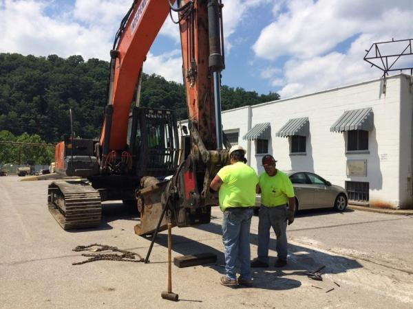 Contractors from Independence Excavating attach a sheer to a backhoe in preparation of demolition at the site.