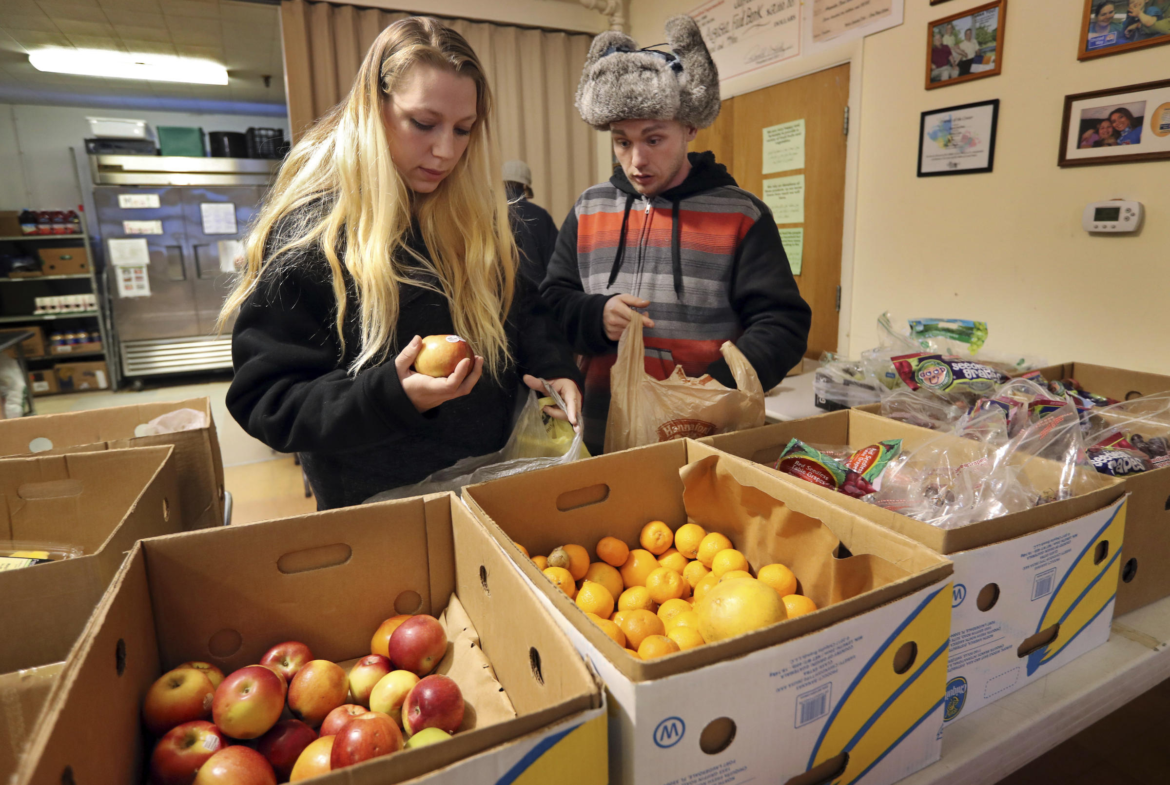 In This Monday March 27 2017 Photo Sunny Larson Left And Zak McCutcheon Pick Produce While Gathering Provisions To Take Home At The Augusta Food Bank