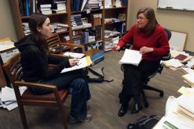 Michelle Drumbl and law student Jessica Unger discuss a client's issue.