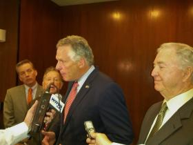 Governor McAuliffe speaks to reporters as budget committee members watch on.