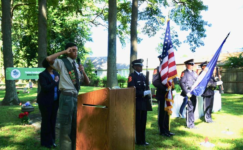Kene Lively, a Tucker descendent and member of Boy Scouts of America Troop 1833, Stone Mountain, Georgia, salutes during a color guard ceremony at his family's cemetery.