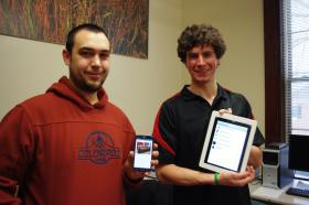 "Miami University senior and computer science major Dave Greiner holds the Android app he's helping develop while The Myaamia Center's Andrew Strack shows off the iPad ""niiki"" app."