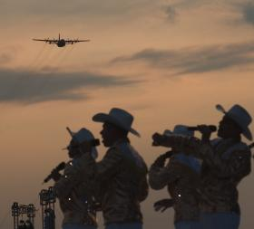 A C-130 Hercules approaches as the U.S. Air Force Tops in Blue perform at a Tattoo June 29.