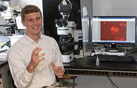 Dirk Auman in the lab; the image on the monitor shows an Arabidopsis plant cell undergoing meiosis, a specialized cell division that produces gamete (sperm and ovules).