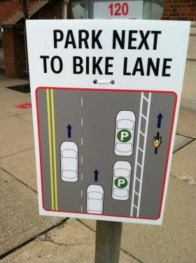 Poster describing parking pattern on Central Parkway with the addition of a new protected bicycle lane.  This sign located behind Music Hall.