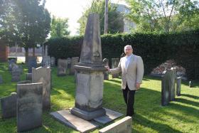 Ed Marks stands beside the Jonas family obelisk.