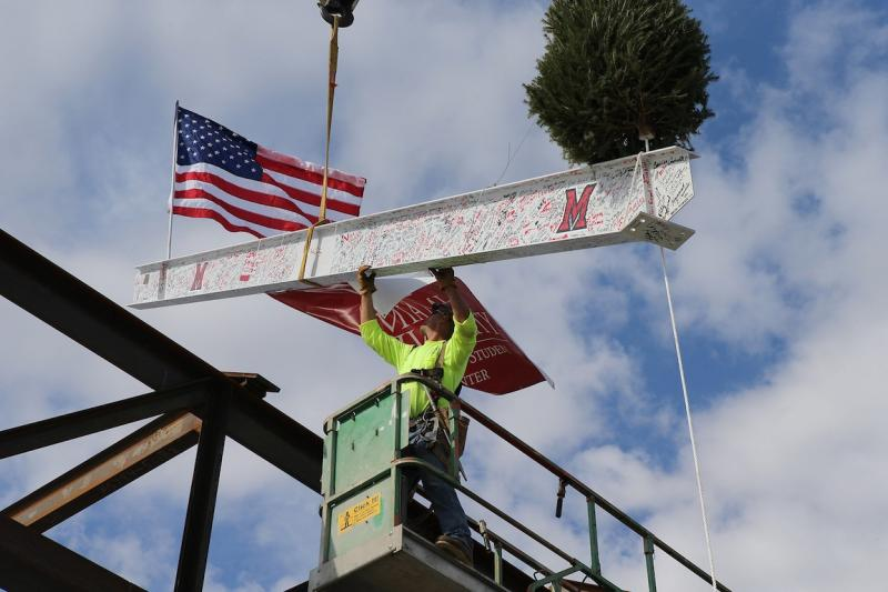 "A worker guides the final steel beam into place during a ""topping out"" ceremony for Miami University's Armstrong Student Center."