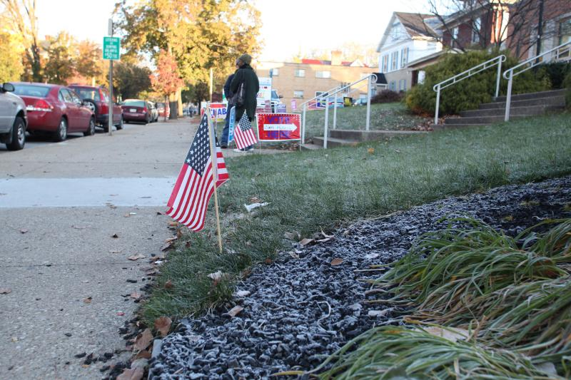 Poll workers and volunteers fight the cold morning to pass out literature and help voters.