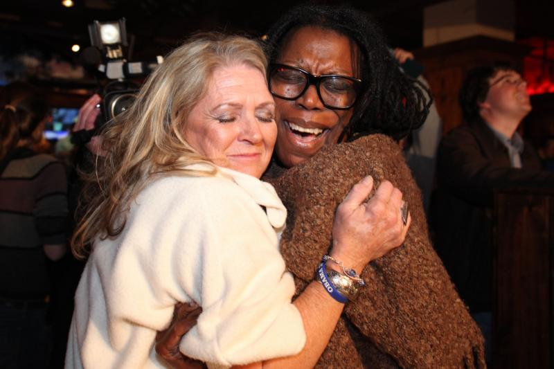 In the midst of an animated crowd, two women embrace after learning of President Obama's lead in the Electoral College.