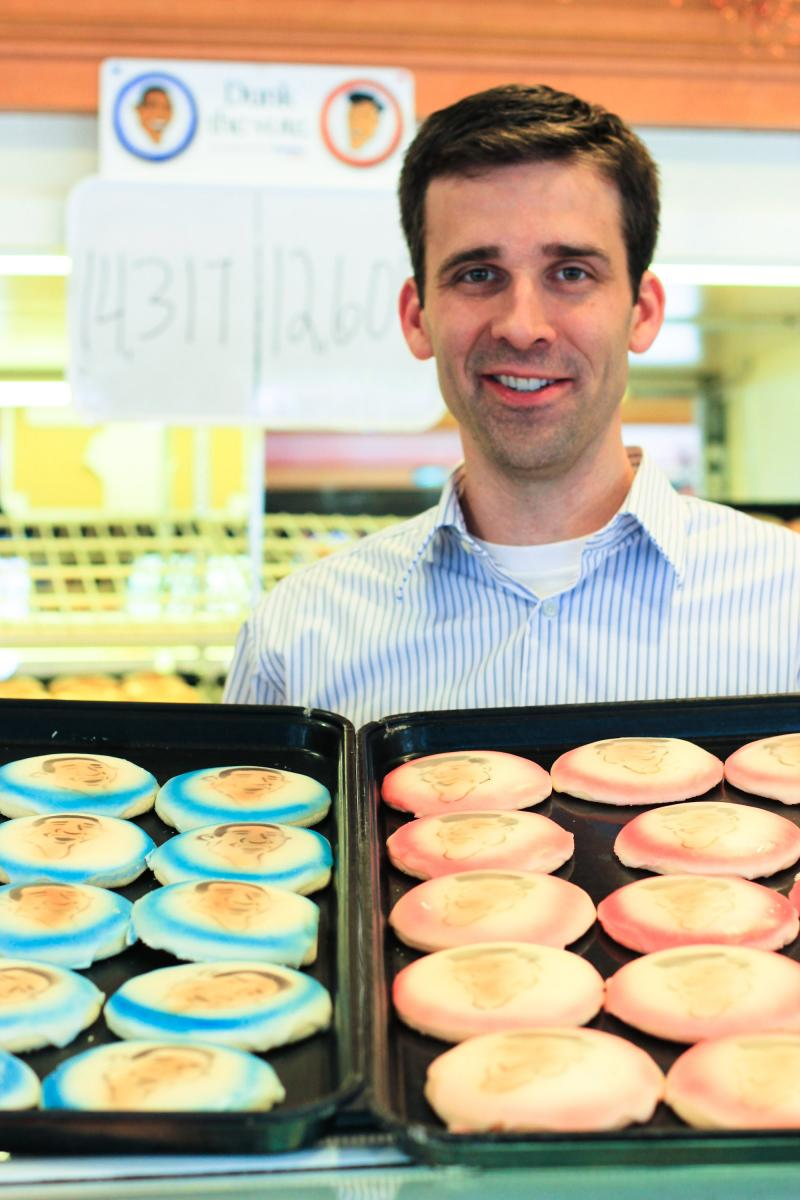 Dan Busken, president and CEO of Busken Bakery, poses with Obama and Romney cookies. Behind him is a count of cookies sales from the past month.
