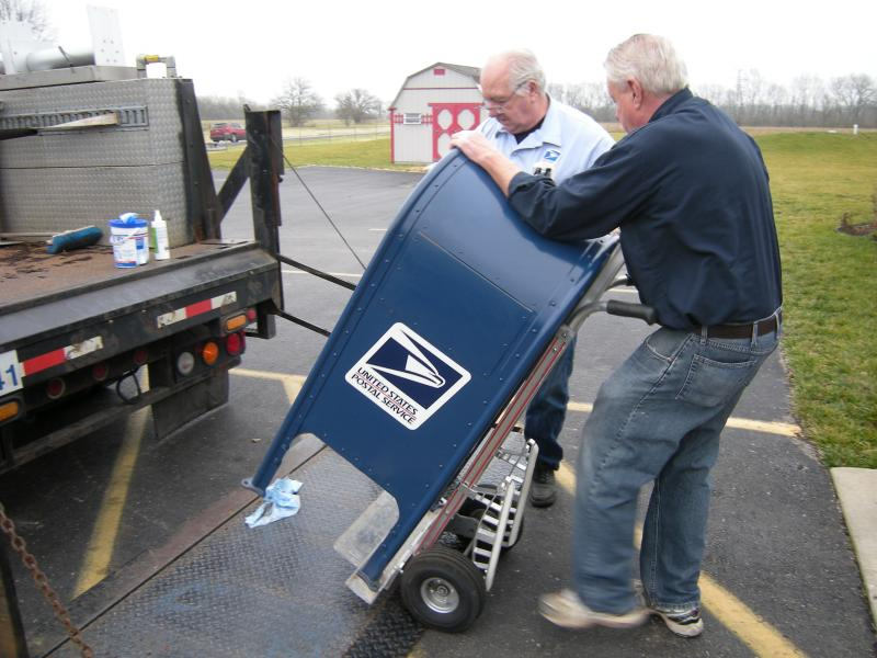 Postal workers carry a new collection box onto the porch of Dunkelberger Lawn and Garden