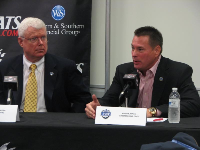 William Webb of the Belk Bowl (L) and UC coach Butch Jones talk with reporters about the December 27 game.