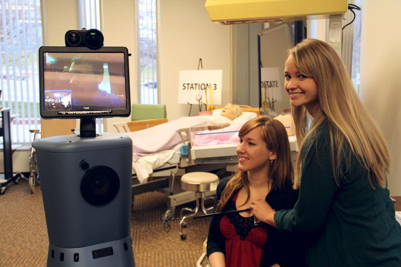 "A couple of students practice on the InTouch RP-7 telehealth robot named ""Flo-Bot,"" in honor of Florence Nightingale"
