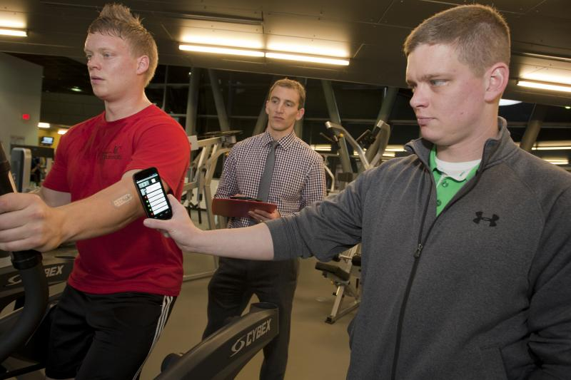 UC researcher Jason Heikenfeld, center, tests the sweat-sensor communication with a smart phone. At right is student Daniel Rose. At left is Dan's brother, Roger Rose.