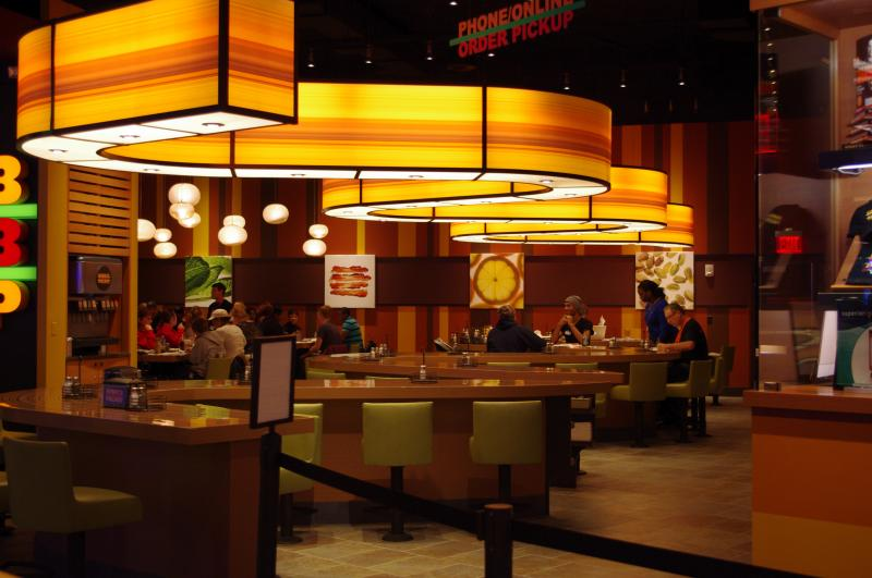 "Celebrity Chef Bobby Flay's ""Bobby's Burger Palace"" offers gourmet burgers along a serpentine bar."