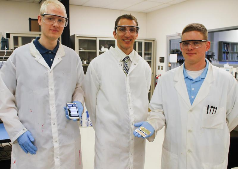 Jason Heikenfeld (center) with two of his students in the lab.