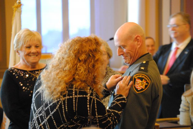 Kimberly Neil pins the sheriff's badge on her husband.