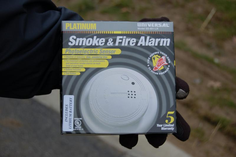 Cincinnati firefighter holding photoelectric smoke detector