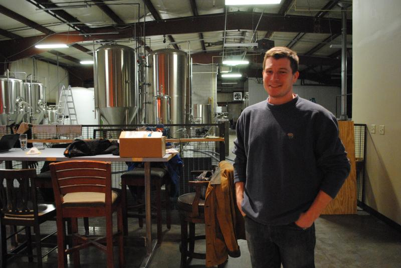 Jeff Hunt stands in front of the mixing tanks that gurgle with Happy Amber Ale