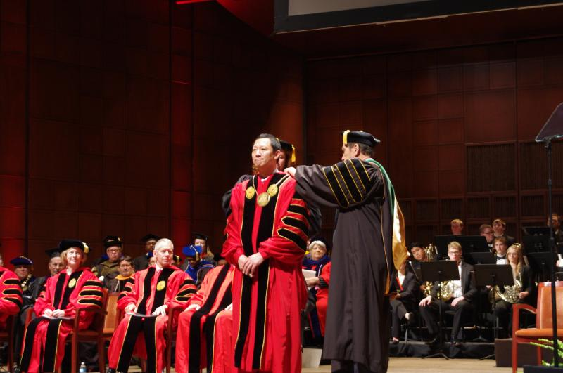 Two university deans present Ono with the presidential medallion.
