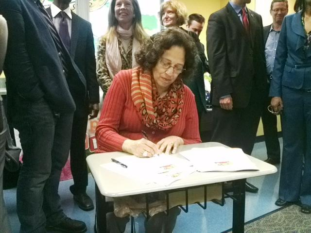 Cincinnati Public Schools Board of Education President Eileen Cooper-Reed signs the Cincinnati Preschool Promise following a news conference at Riverview East Academy.