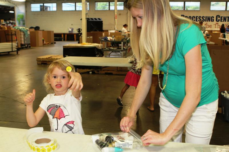 Jen VanHorn and 5-year-old daughter Emmaline fill bags of personal care items for shipment to disaster areas.
