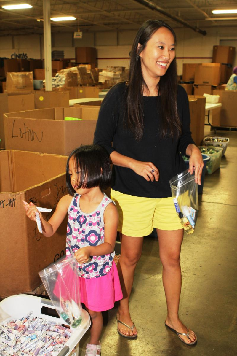 Grace Wu and 4-year-old daughter Ellie work together to fill personal care kits.