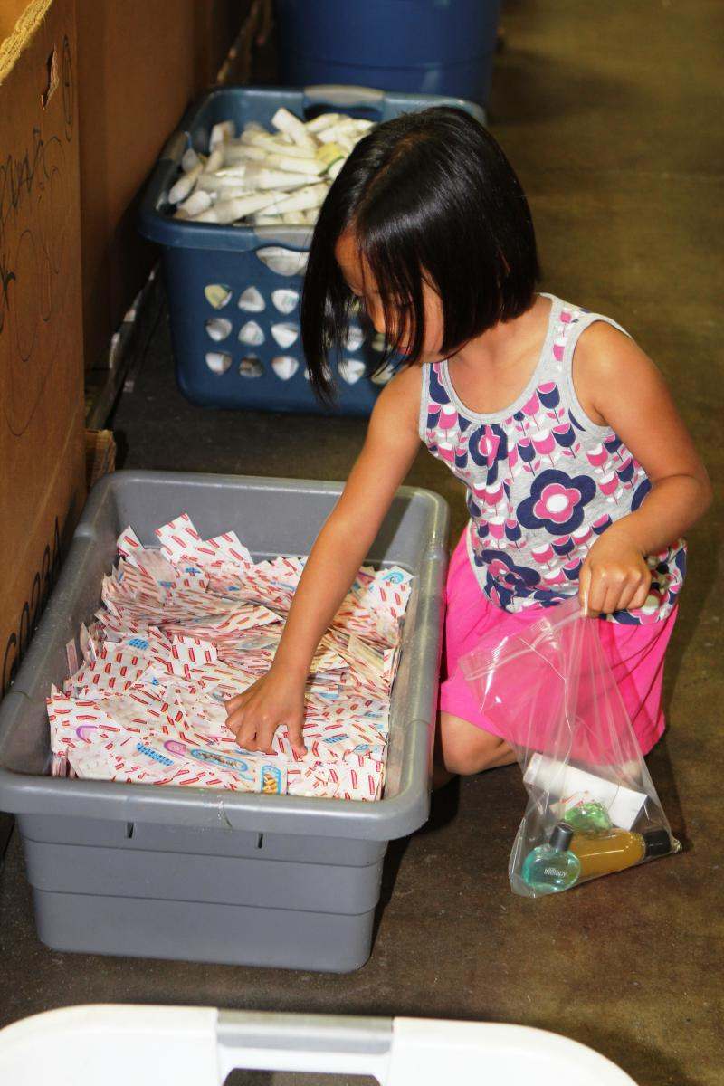 Ellie Wu puts bandages in a personal care kit.