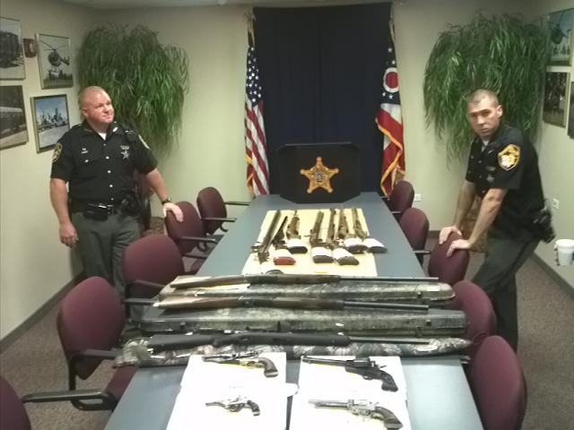 Deputies layout 15 guns collected from one sex offender's home.