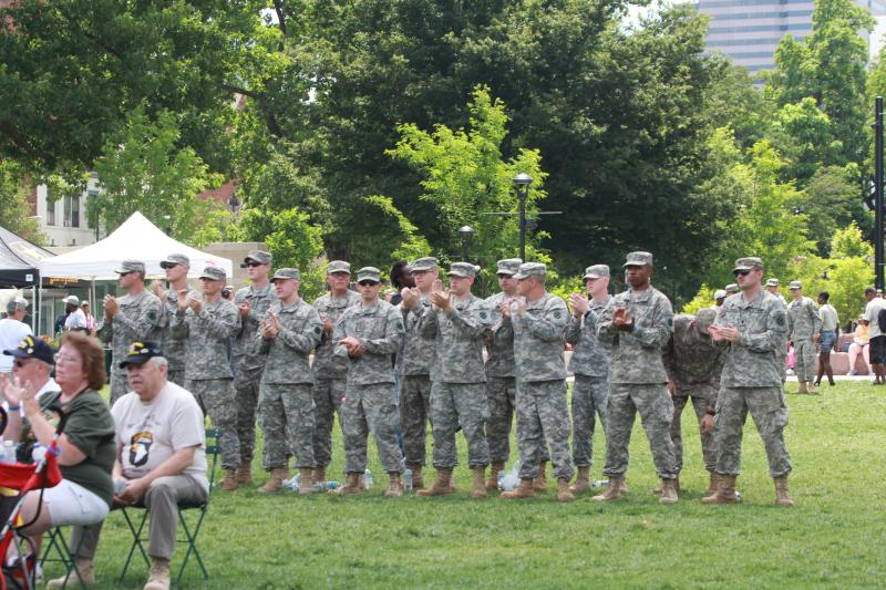 Active duty and retired military members join family and community celebration in Washington Park Friday.