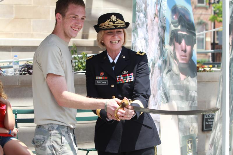 Brigadier General Margaret Burcham and a recruit cut the Army cake with a ceremonial sword.
