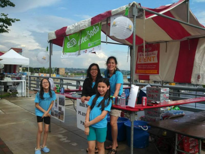 Emiko Moore (right) and her daughter Miya (front) raise awareness at Cincinnati's Asian Food Fest.