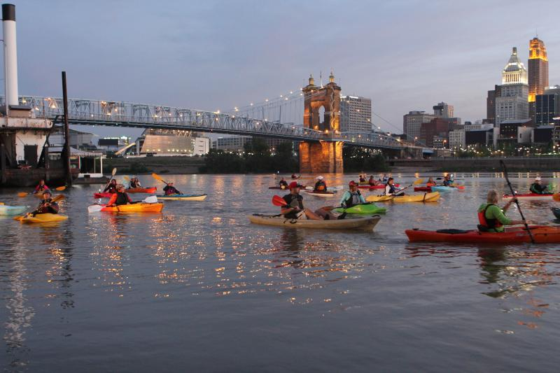 A group of about 30 kayakers takes to the water as the sky grows lighter.